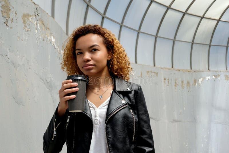 Uma mulher afro-americano nova moderna bonita em um casaco de cabedal guarda um vidro preto na mão na perspectiva de um o foto de stock