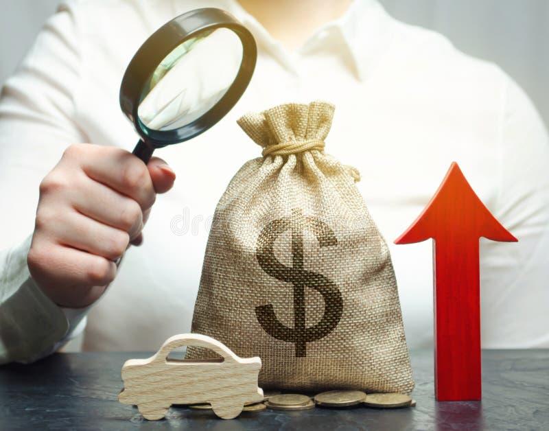 Uma mulher analisa os preços para a compra dos veículos O custo da auto manutenção está aumentando Taxas de juro altas para imagem de stock