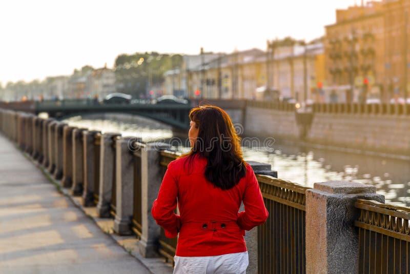Uma mulher anda através da cidade velha foto de stock royalty free