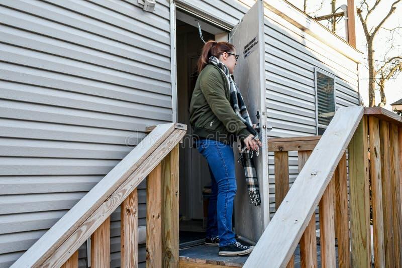 Uma mulher anda para fora sua porta da rua a sair em casa imagem de stock