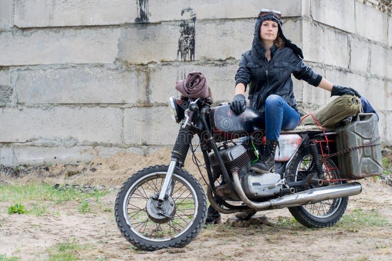 Uma mulher apocalíptico do cargo na motocicleta perto da construção destruída fotos de stock royalty free