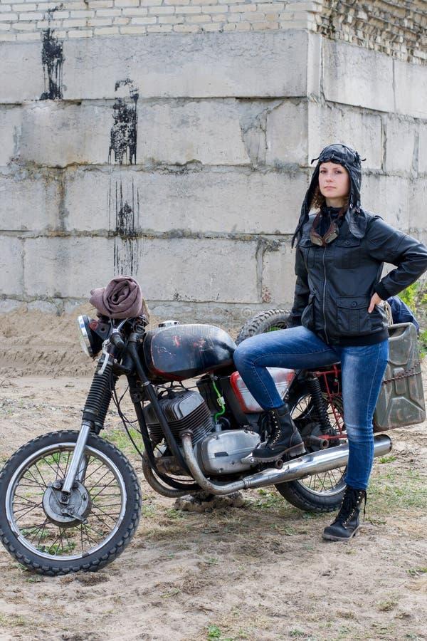Uma mulher apocalíptico do cargo perto da motocicleta perto da construção destruída foto de stock royalty free