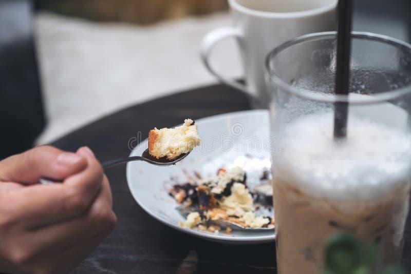 Uma mulher aprecia comer o bolo de queijo e o café no café fotografia de stock royalty free