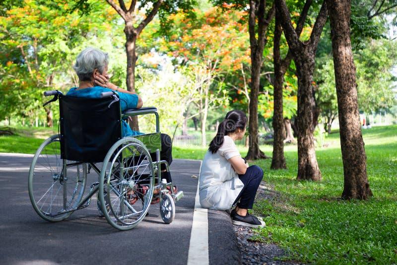 Uma mulher asiática adulta que se sente sensível e zangada agindo com idosos em cadeira de rodas após discussão sobre a mãe sênio fotografia de stock royalty free