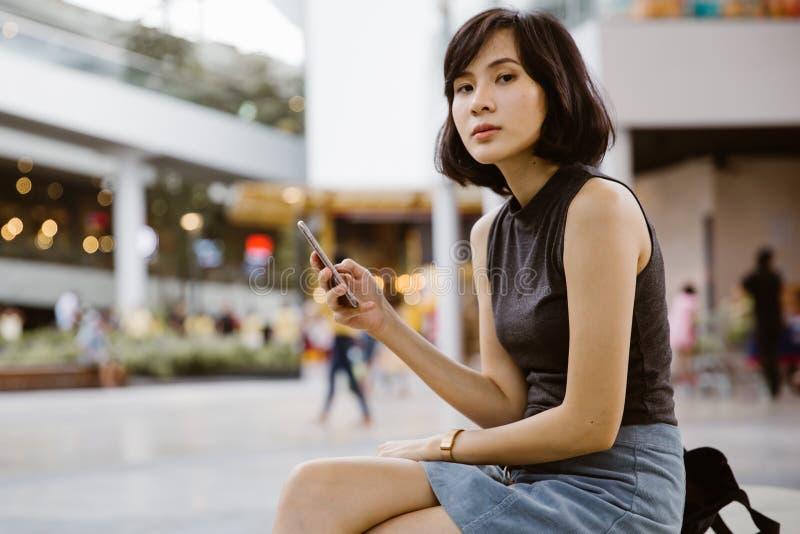 Uma mulher asiática bonita atrativa que usa o telefone de mobil aos sms imagem de stock royalty free