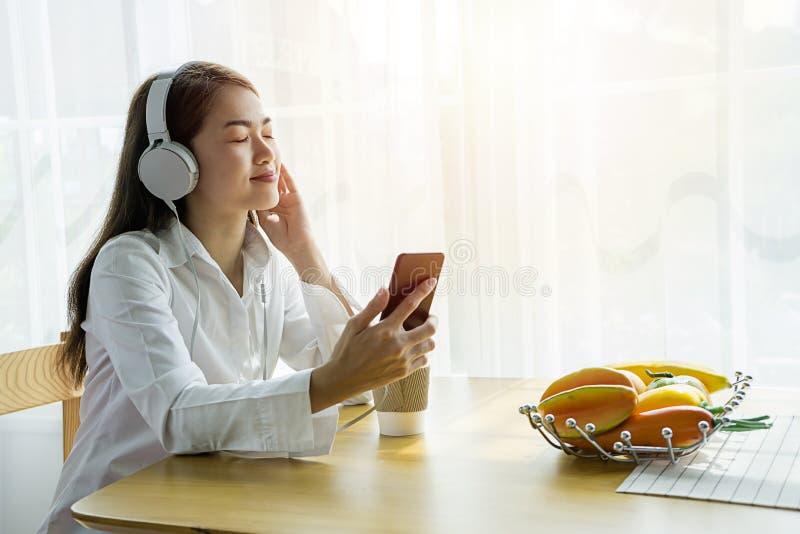 Uma mulher asiática bonita está escutando a música felizmente em sua casa fotografia de stock