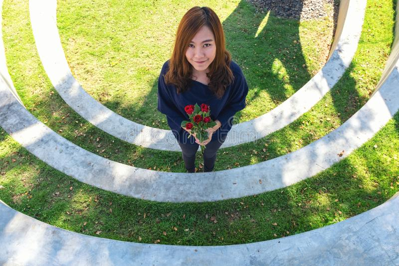Uma mulher asiática bonita que guarda rosas vermelhas floresce foto de stock