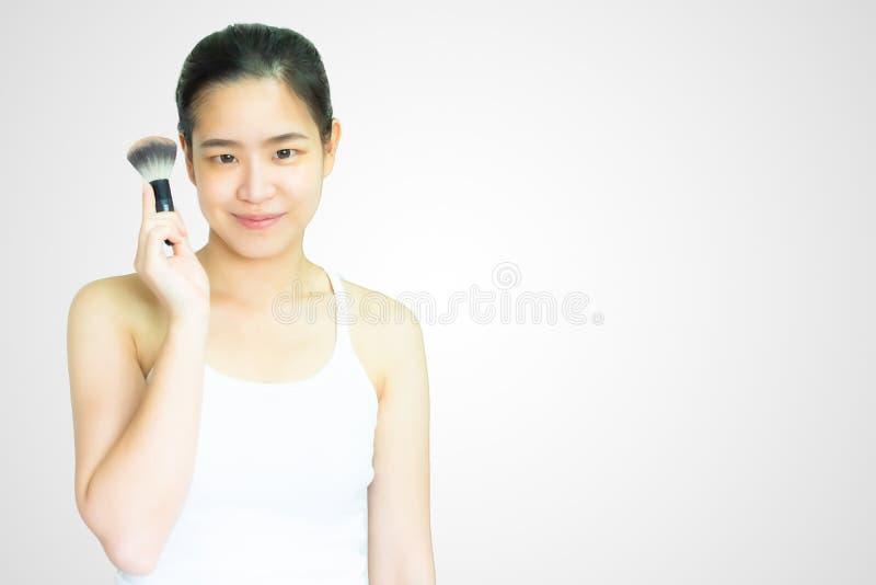 Uma mulher asiática está guardando o brushon no fundo branco imagem de stock