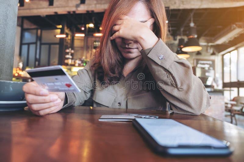 Uma mulher asiática que guarda o cartão de crédito com sentimento forçou e quebrou foto de stock royalty free