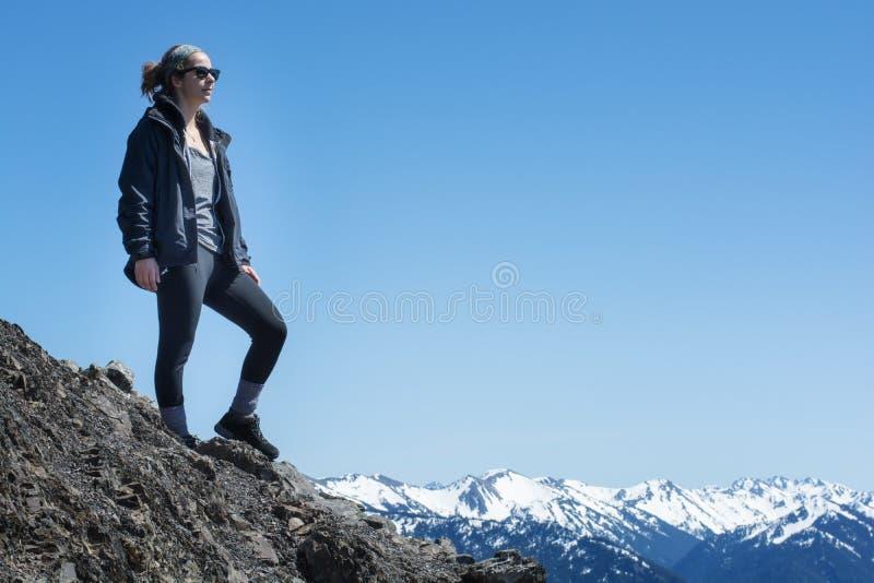 Uma mulher atlética ativa está na parte superior de uma montanha imagens de stock
