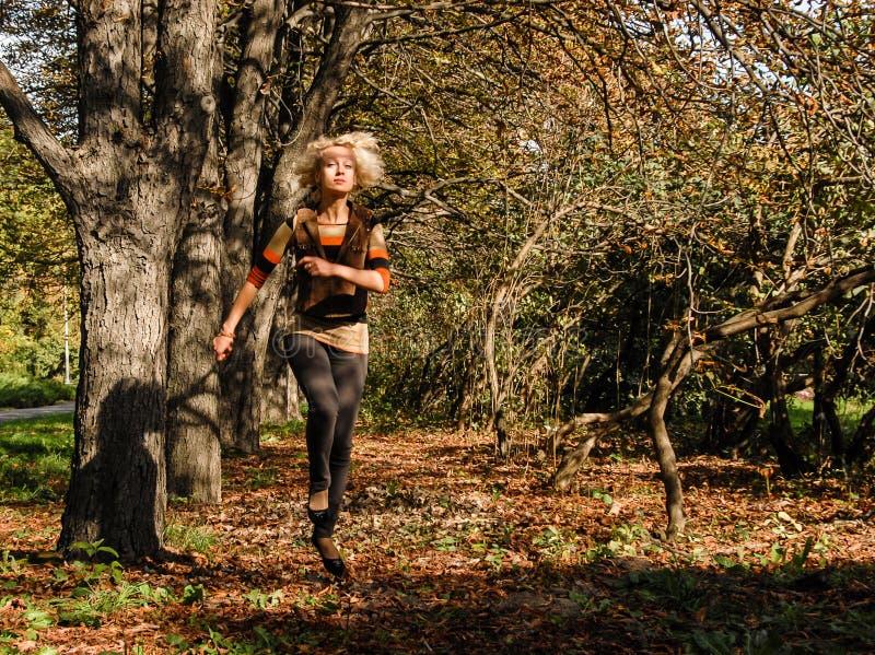 Uma mulher atlética nova corre o salto no parque e olha feliz fotografia de stock