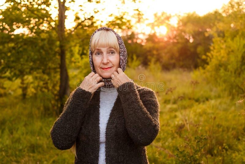 Uma mulher atrativa da idade da reforma endireita seu lenço em seus cabeça e olhares na câmera no contra a luz do por do sol fotografia de stock