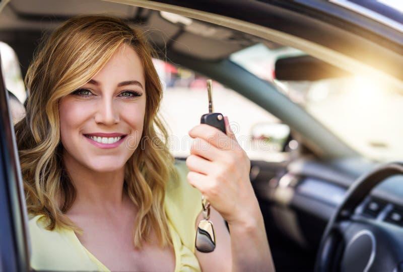 Uma mulher atrativa em um carro guarda uma chave do carro em sua mão fotos de stock