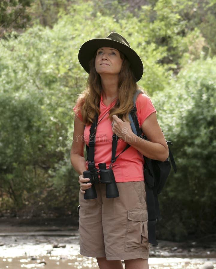 Uma mulher atrativa que Birdwatching por um rio fotografia de stock royalty free