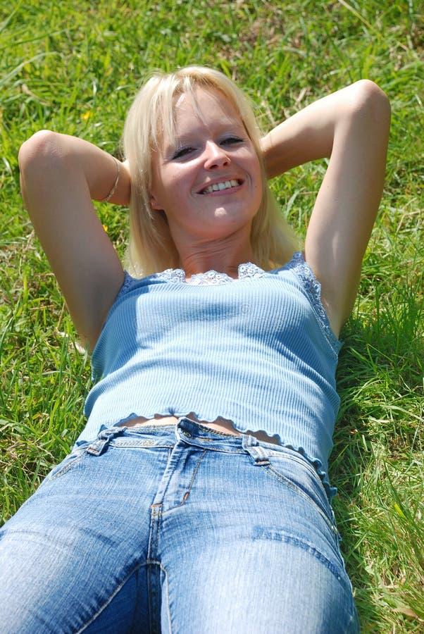 Uma mulher bonita adormecida em um campo gramíneo imagens de stock