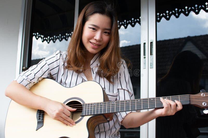 Uma mulher bonita asiática está jogando a guitarra foto de stock royalty free