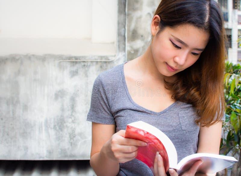 Uma mulher bonita asiática está lendo um livro imagens de stock royalty free