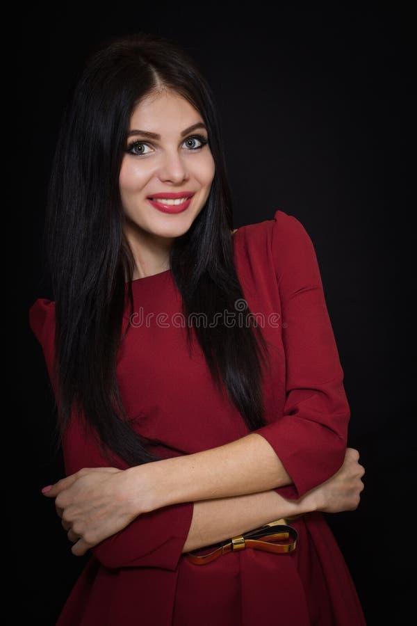 Uma mulher bonita com cabelo reto preto e os olhos azuis em uma Borgonha vestem-se foto de stock royalty free