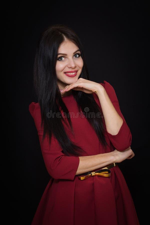 Uma mulher bonita com cabelo reto preto e os olhos azuis em uma Borgonha vestem-se fotografia de stock