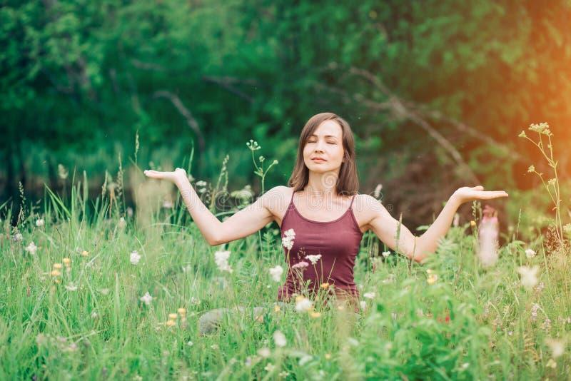 Uma mulher bonita com palmas abertas com um sorriso que olha a câmera no esclarecimento A saúde, ioga, harmonia, relaxa imagem de stock