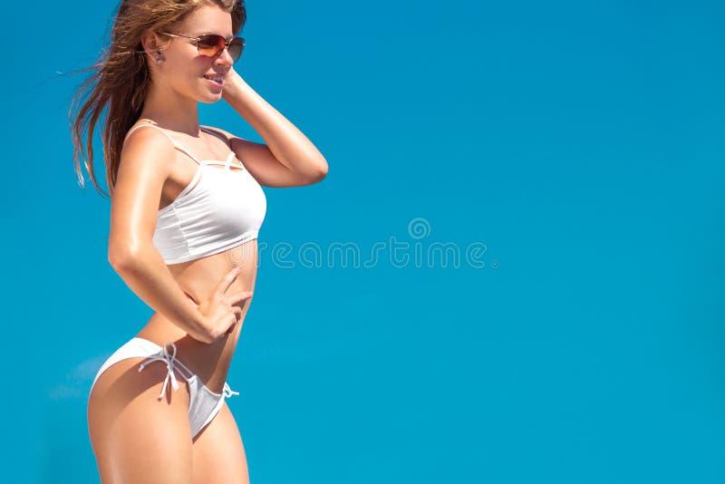 Uma mulher bonita da aptidão no roupa de banho branco sobre o fundo do mar no verão Conceito do esporte e da beleza imagens de stock royalty free