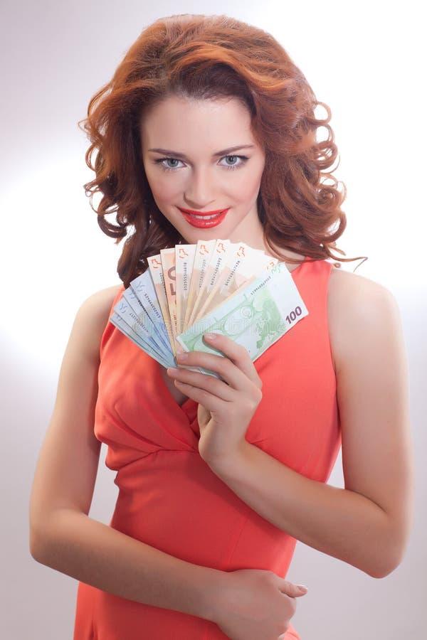 Uma mulher bonita em um vestido cor-de-rosa com as euro- cédulas nas mãos fotos de stock royalty free