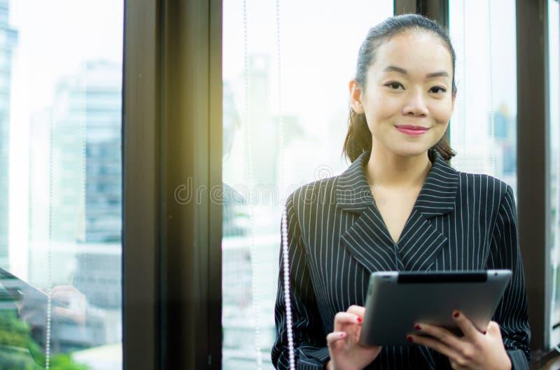 Uma mulher bonita está estando ao lado da janela imagem de stock