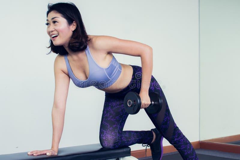 Uma mulher bonita está fazendo o exercício no gym imagens de stock