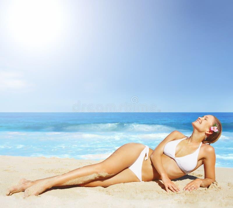 Uma mulher bonita no biquini que sunbathing na praia fotografia de stock