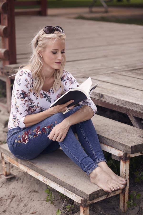 Uma mulher bonita nova, 25 anos velha, lendo um livro, assoalho de madeira, fora calças de brim vestindo, parte superior floral d fotografia de stock royalty free