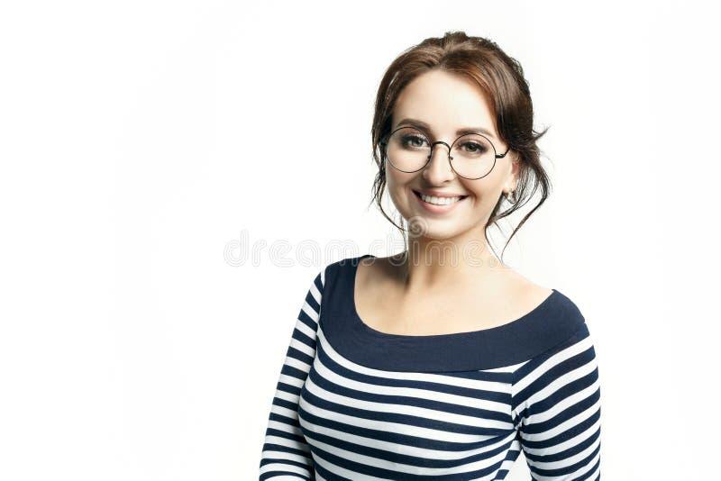 Uma mulher bonita nova em uma blusa apertada listrada e em vidros redondos sorri extensamente os dentes brancos fotos de stock