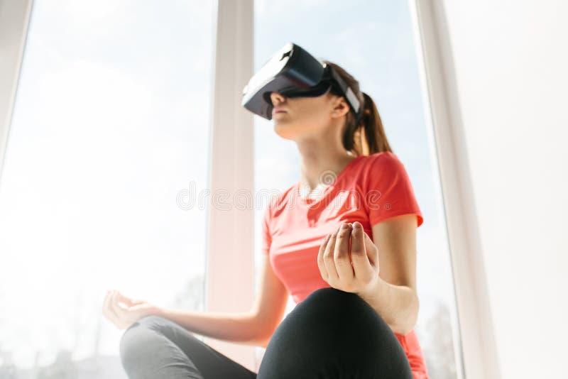 Uma mulher bonita nova em vidros da realidade virtual faz a ginástica aeróbica remotamente Conceito futuro da tecnologia Classes  fotos de stock