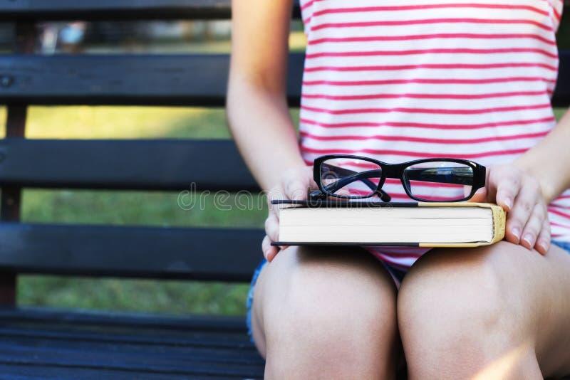 Uma mulher bonita nova que senta-se no livro do banco e de leitura no parque A menina bonita está fora no dia de verão fotos de stock royalty free