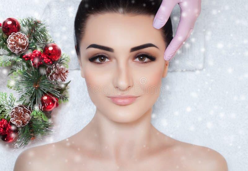 Uma mulher bonita obtém uma massagem facial no salão de beleza dos termas Close up da cara da mulher e da grinalda do ano novo imagens de stock royalty free