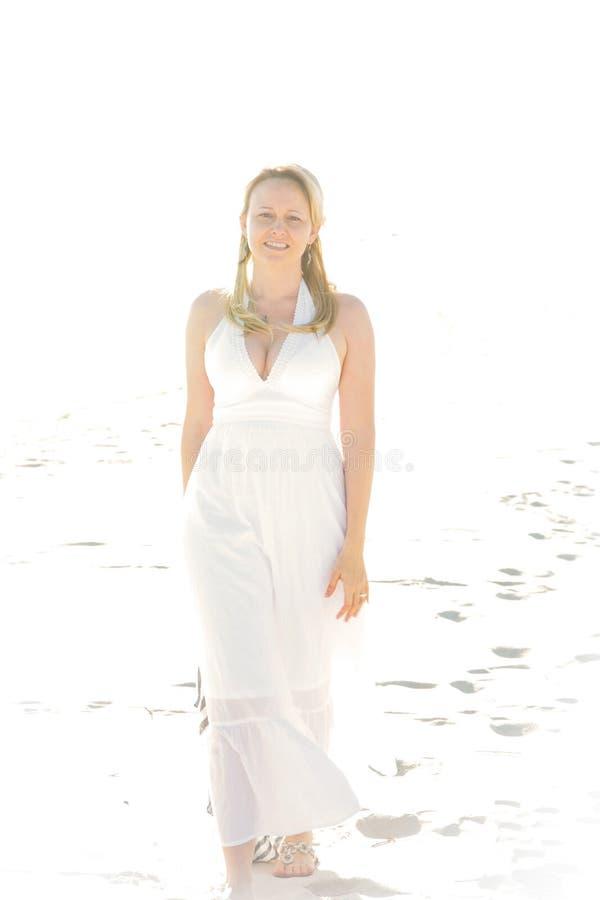 Uma mulher bonita que anda no Sun fotos de stock royalty free