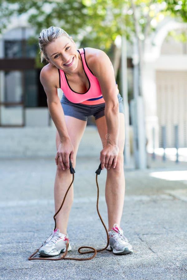 Uma mulher bonita que faz a corda de salto imagens de stock