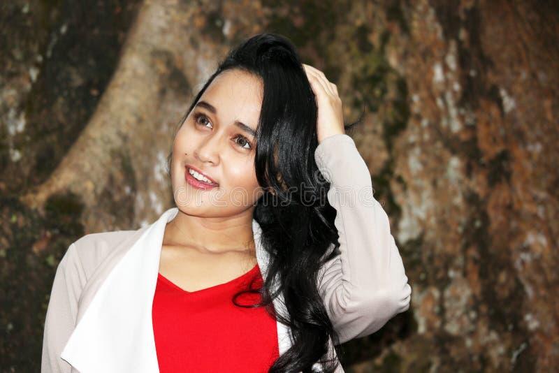 Uma mulher bonita que sorri sob a árvore grande fotografia de stock
