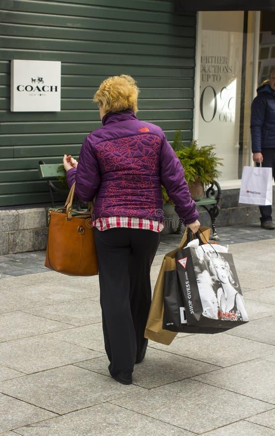 Uma mulher carregado com sacos de portador ao apreciar alguma terapia varejo na tomada ascendente da compra da vila de Kildare do fotografia de stock