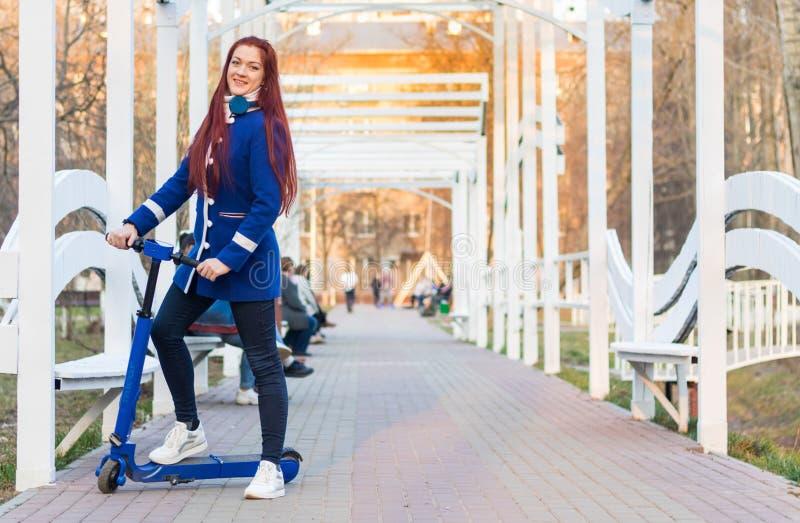 Uma mulher caucasiano nova com cabelo vermelho em um revestimento azul em um 'trotinette' el?trico azul no parque transporte Eco- fotos de stock