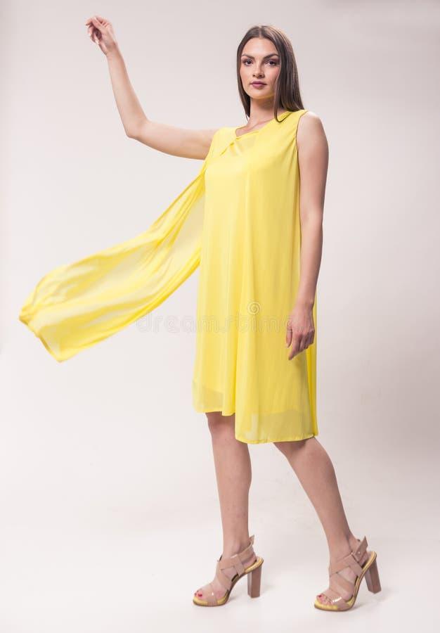 Uma mulher caucasiano nova, estúdio, fundo branco, dres amarelos imagem de stock