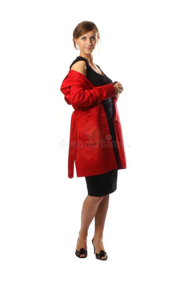 Uma mulher caucasiano nova que levanta em um revestimento vermelho fotografia de stock royalty free