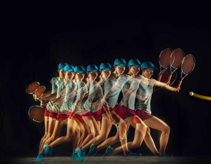 Uma mulher caucasiano que joga o tênis no fundo preto em luz misturada imagens de stock