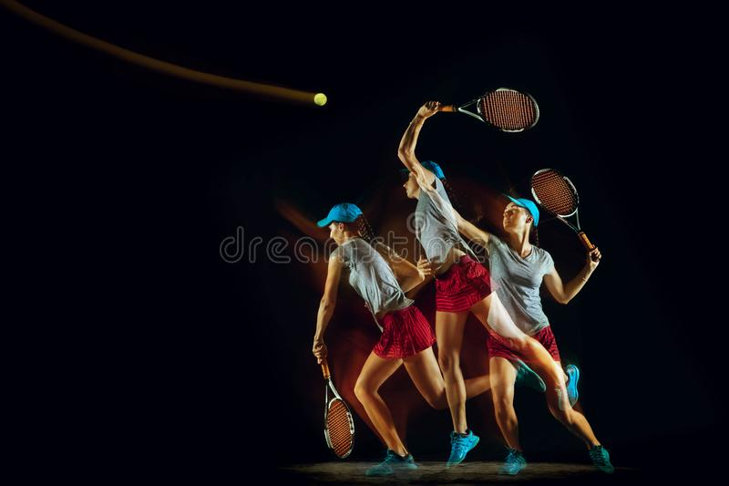 Uma mulher caucasiano que joga o tênis no fundo preto em luz misturada imagens de stock royalty free