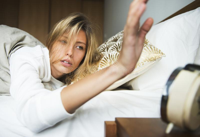 Uma mulher caucasiano sonolento que desliga um alarme foto de stock royalty free