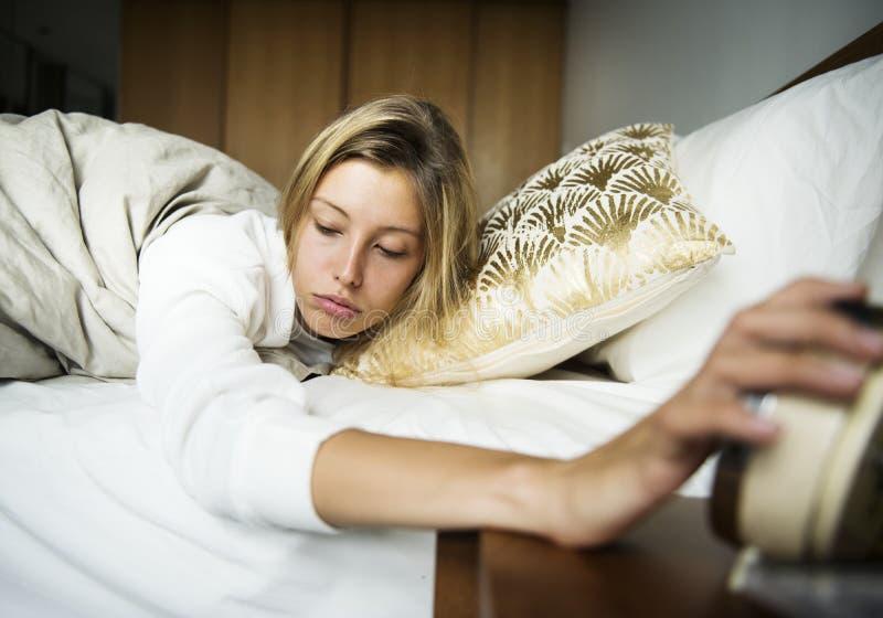 Uma mulher caucasiano sonolento que desliga um alarme imagem de stock