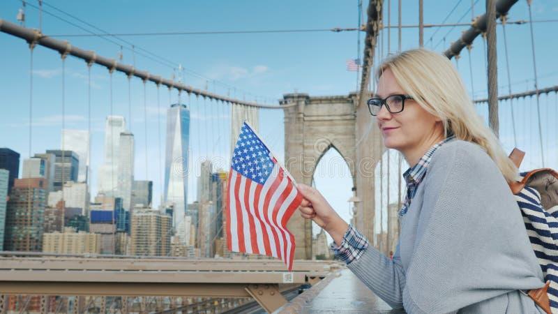 Uma mulher com a bandeira de América em seus suportes da mão na ponte de Brooklyn com uma vista de Manhattan Turismo nos EUA imagens de stock royalty free