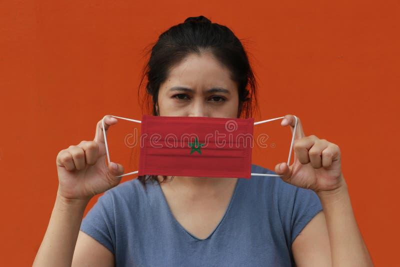 Uma mulher com a bandeira marroquina na sua mão e levantada na frente do rosto sobre fundo cor de laranja Partícula fina ou imagens de stock
