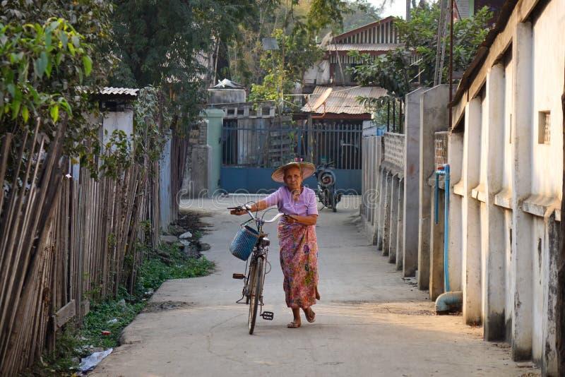 Uma mulher com a bicicleta na rua em Hsipaw imagem de stock royalty free