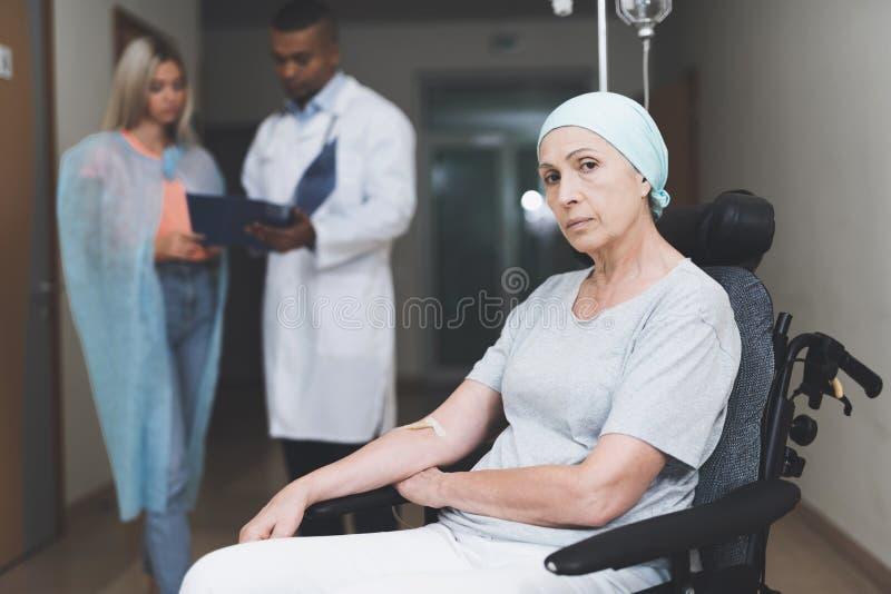 Uma mulher com câncer, com um olhar condenado, está sentando-se em uma cadeira de rodas Atrás de sua filha está e fala ao doutor foto de stock