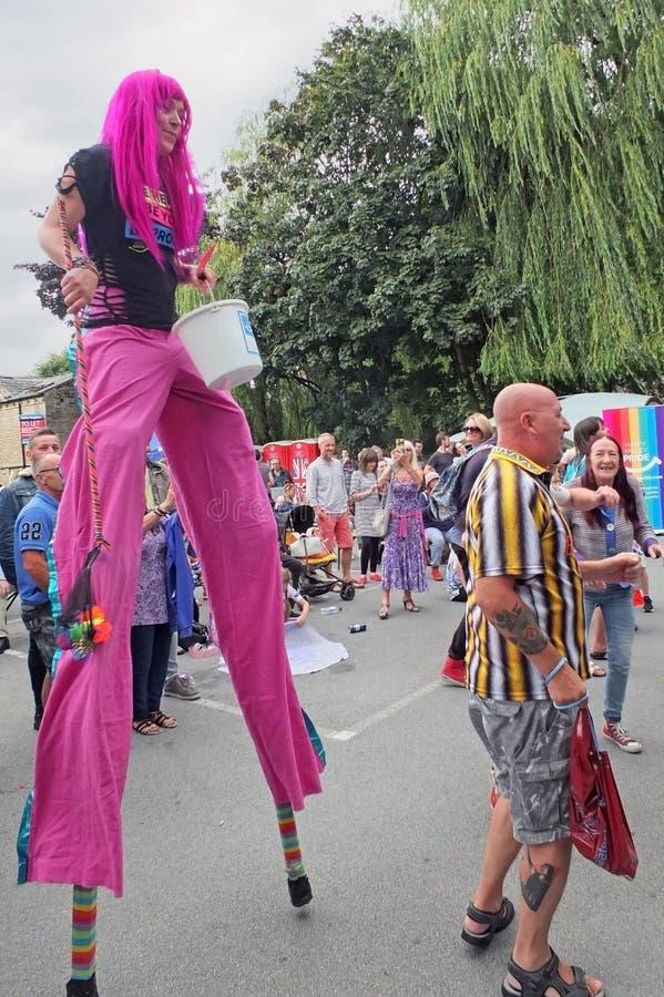 Uma mulher com cabelo cor-de-rosa em pernas de pau e os povos que dançam no vale feliz orgulham-se o evento hebden dentro a ponte fotos de stock